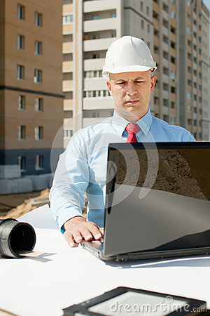 Architect works in front of building site