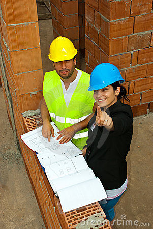Architects with blueprints pointing up