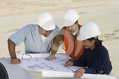 Architects Examining Blueprint At Site