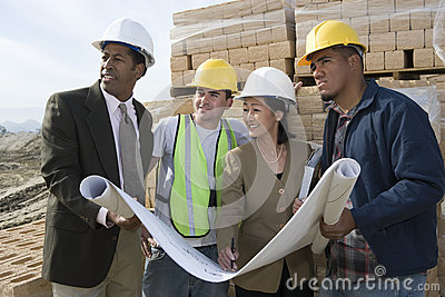 Architects And Workers With Blueprint At Site