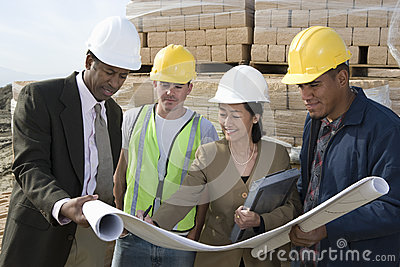Architects And Workers In Discussion At Site