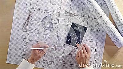 Architetto che per mezzo del calcolatore sul piano architettonico della costruzione di casa del modello con la matita, il righell stock footage