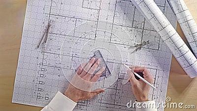 Architetto che prende le misure sul piano architettonico della costruzione di casa del modello con la matita, il righello, le bus stock footage