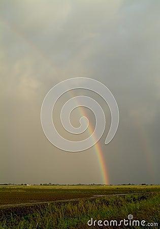 Arco iris sobre tierras de labrantío planas