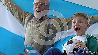 Argentinien lockert zujubelndes Lieblingsteam, Jungen mit aufpassendem Fußball des Großvaters auf stock video footage