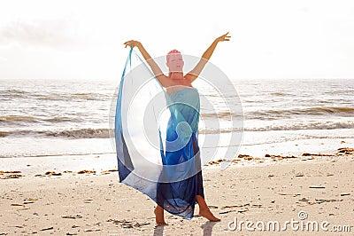 Arms raised on beach