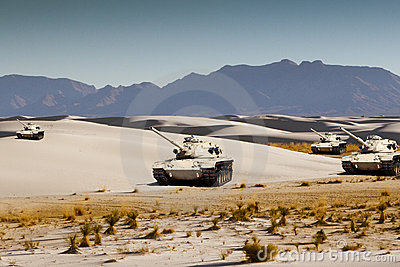 Army tanks maneuver in the white desert sand