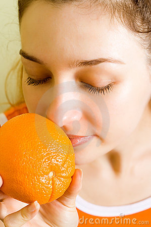 Aroma fruit therapy - woman smelling orange