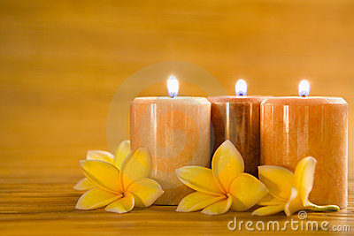 Aromatic candles with frangipani on bamboo mat