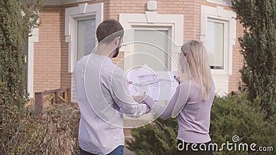 Arquiteto Caucasiano masculino e sua assistente feminina examinando projetos em frente à casa e dando cinco video estoque