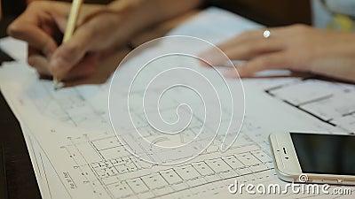 Arquiteto das mulheres que trabalha com folhas, disposições e desenhos do modelo dos locais Mulher no trabalho filme