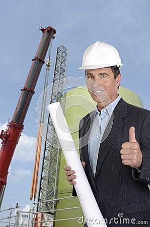 Arquiteto masculino no sorriso e no polegar do canteiro de obras acima