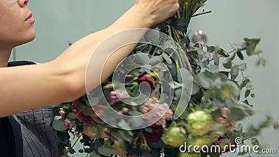 Arranger λουλουδιών τυλίγει μια στρογγυλή ανθοδέσμη γύρω με μια σκούρο πράσινο κορδέλλα απόθεμα βίντεο