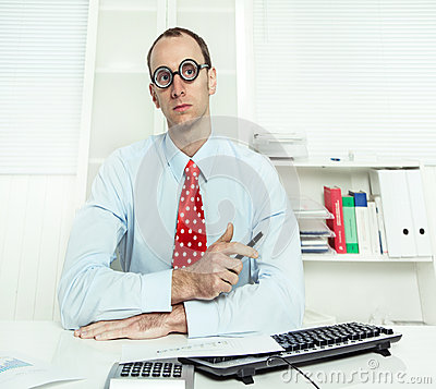 Arrogant man sitting at desk with glasses, a red tie and a blue
