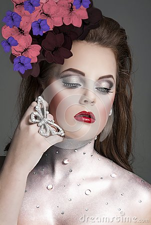Art of makeup, model with jeweled silver neck and glitter.