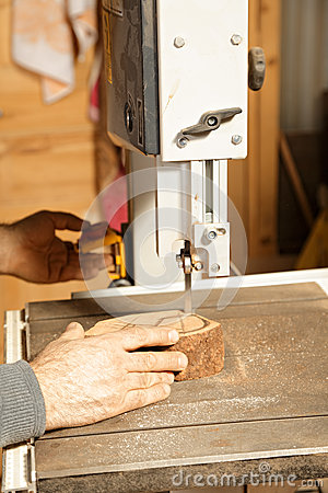 Artisan hands sawing billet