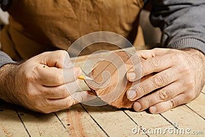 Artisan hands sketching on wood billet