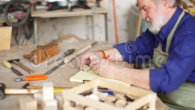 Artisan sasseyant sur le bureau en bois avec de divers instruments
