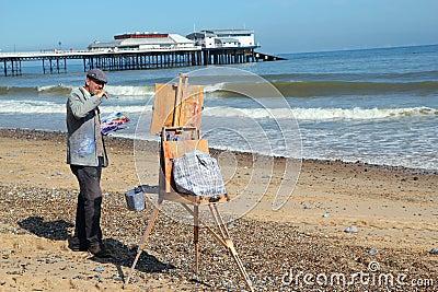 Artist on a beach.