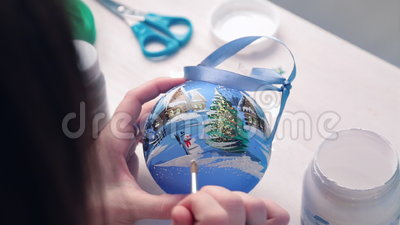 The artist draws on ball. The artist draws on Nativity Christmas tree ball stock footage