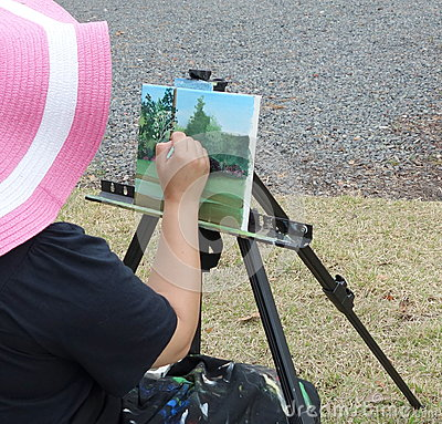 Artist lady sitting and painting on canvas outside.