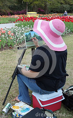 Artist lady sitting and painting outdoors.