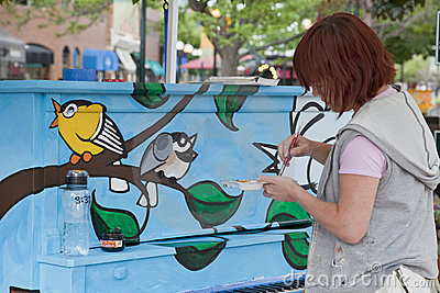 Artist painting mural on the piano Editorial Image