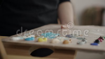 Artist palette with oils. Close-up shot of woman artist taking oils paints from the wooden palette stock footage