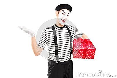 Artista maschio del mimo che tiene un contenitore di regalo e che gesturing con la sua mano