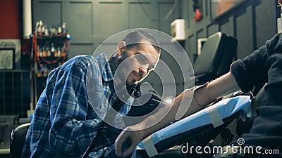 Artista maschio nel corso della fabbricazione del tatuaggio nel suo salone stock footage