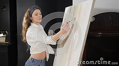 Artiste féminine sérieuse travaillant sur une photo avec des peintures à l'huile et créant une image abstraite sur toile Techniqu banque de vidéos