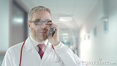 Arts praat met een patiënt op zijn mobiele telefoon in een ziekenhuisgang stock footage