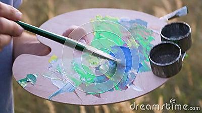 Artysta miesza kolor na palecie w otwartej przestrzeni wśród naturalnego krajobrazu Widok zamykający paletę i pędzel zbiory