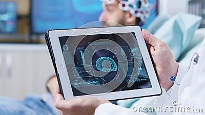 Arzt in einer modernen Klinik, die eine Tablette mit Gehirnanalyse enthält stock video footage