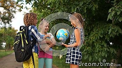 As crianças em idade escolar consideram um grande globo nas ruas após a escola. Estudo de geografia, sonhos de viagem vídeos de arquivo