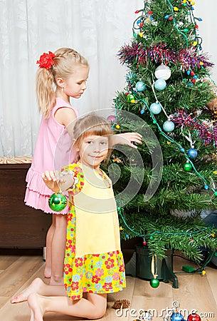 As crianças decoram a árvore de Natal