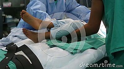 As enfermeiras que transportam-se da cama de hospital na sala de operação à marquesa da maca colocam à área de recuperação filme