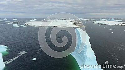 As geleiras e os fragmentos dos iceberg flutuam em torno da ilha rochosa Andreev filme