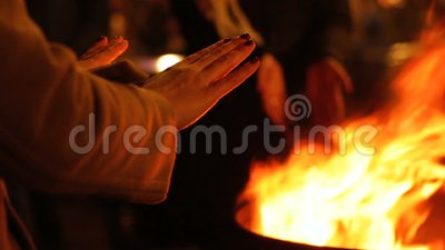 As mãos de aquecimento dos povos aproximam o fogo no festival da rua, celebração dos feriados de inverno video estoque