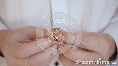 As mãos do homem seguram um velho anel de gemstone dourado video estoque