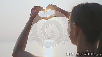 As mãos fêmeas que fazem o gesto da forma do coração que guarda o sol alargam-se video estoque
