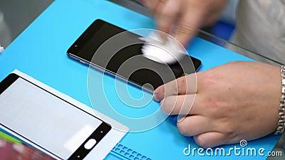 As mãos masculinas que guardam e que limpam uma tela do telefone celular para pôr sobre, aplicam um vidro moderado protetor para  filme