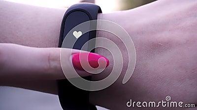 As meninas vestiram um bracelete da aptidão A menina verifica o pulso no podômetro do bracelete da aptidão ou do perseguidor da a video estoque