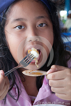 Asain girl eating sea shell grill with fork
