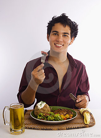 Asian American man with bite a steak