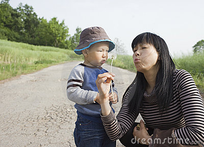 Asian baby boy playing dandelion with his aunt