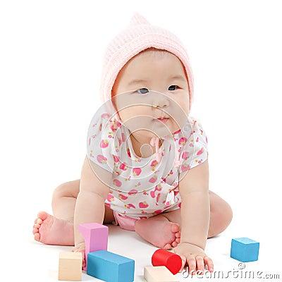 Asian baby girl playing wood blocks