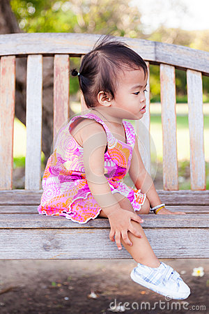 Asian baby girl sitting on bench