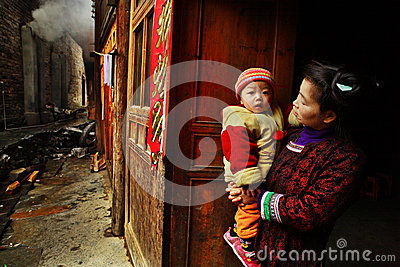 Asian with baby in her arms, stands on rural street. Editorial Image
