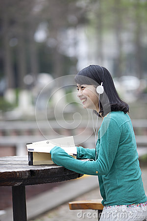 Asian beatiful student reading book in campus